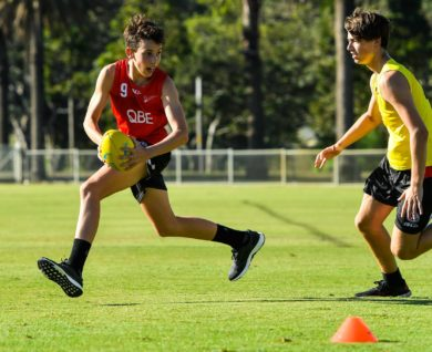 QBE Sydney Swans Academy Payer running with ball chased by opposition