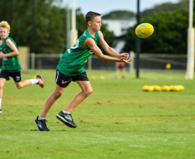 QBE Sydney Swans Academy Youth player handballing football