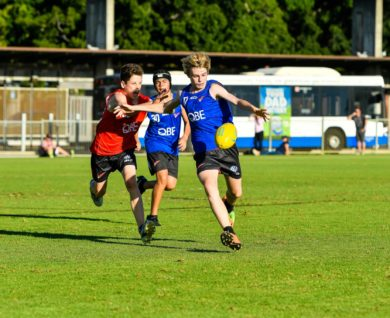 QBE Sydney Swans Academy Player kicking football chased by two other players
