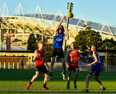 QBE Sydney Swans Academy youth boys player marking football with three other players