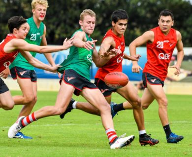 QBE Sydney Swans Academy youth boys player getting tackled whilst trying to kick football