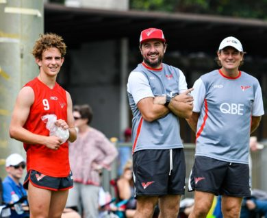QBE Sydney Swans Academy players and coaches smiling watching game