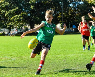 QBE Sydney Swans Academy youth boys player kicking football