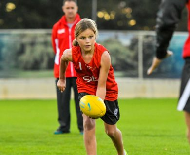 QBE Sydney Swans Academy Youth Girls player handballing football